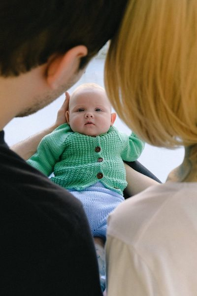 couple holding baby in green